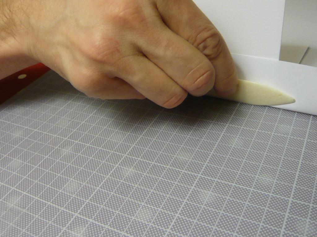 plier : le long de la règle, avec une page de protection et le plioir