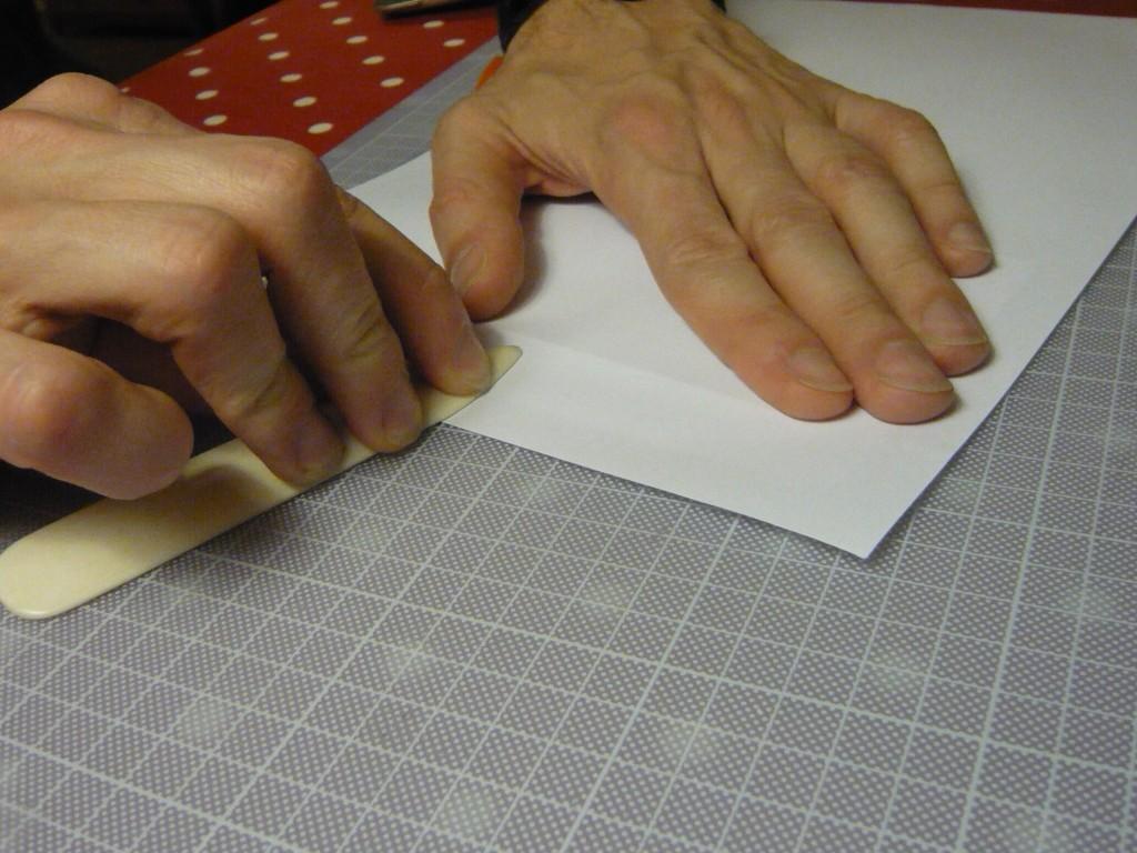 aplatir : avec une feuille de protection et le plioir à plat